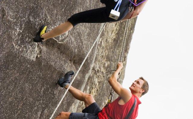 Couple rock climbing on steep cliff