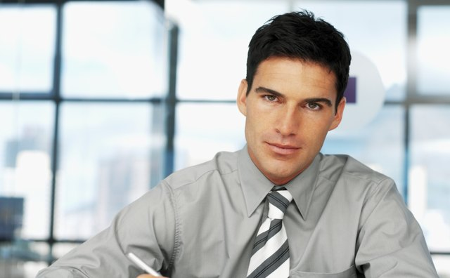 Portrait of a young businessman sitting at a table with a pen and paper