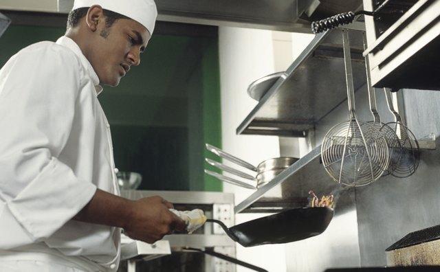Chef sauteing in restaurant kitchen,side view