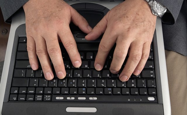 Businessman's hands on laptop computer keyboard, close-up