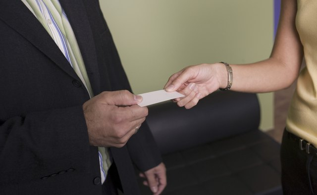 Businesswoman giving a business card to a businessman