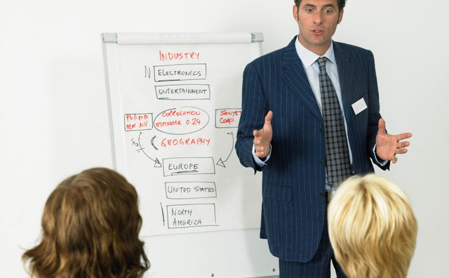 Businessman giving presentation, colleagues in foreground