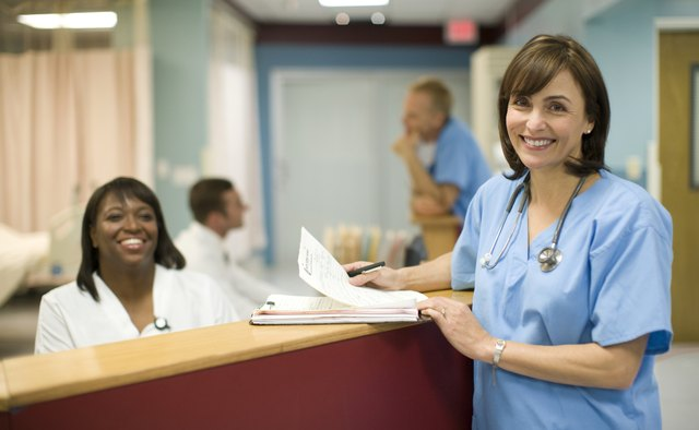 Female doctor with receptionist in hospital, smiling, portrait