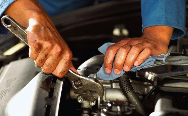 Hands of mechanic fixing engine