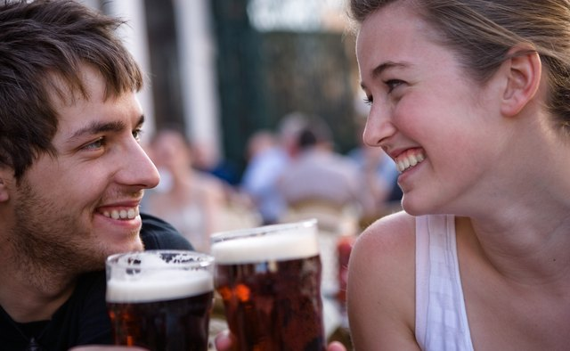 Young woman and man toasting beers outdoors