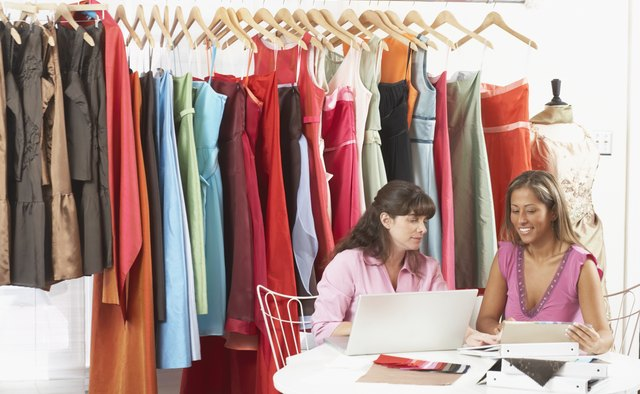 Two young women working on a laptop in a clothing store