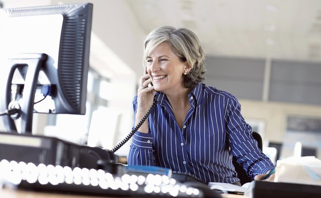Mature woman using telephone at desk in office, smiling