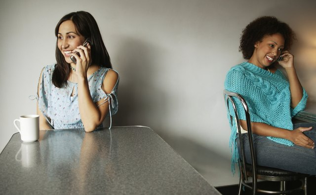 Portrait of two young women talking on mobile phones
