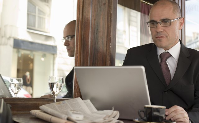 Mature businessman sitting  outside cafe using laptop