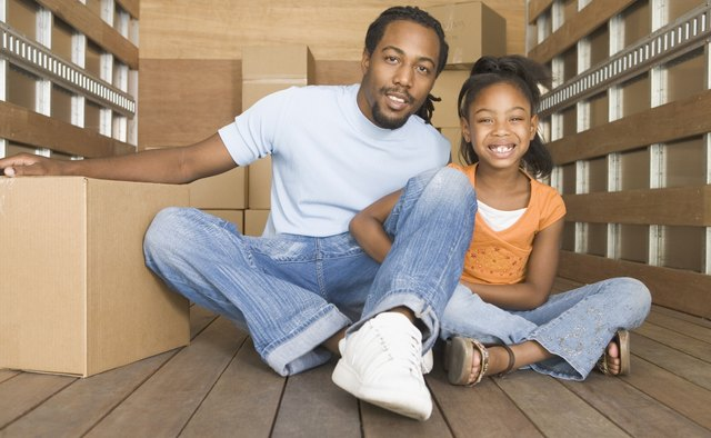 African father and daughter smiling in back of moving truck