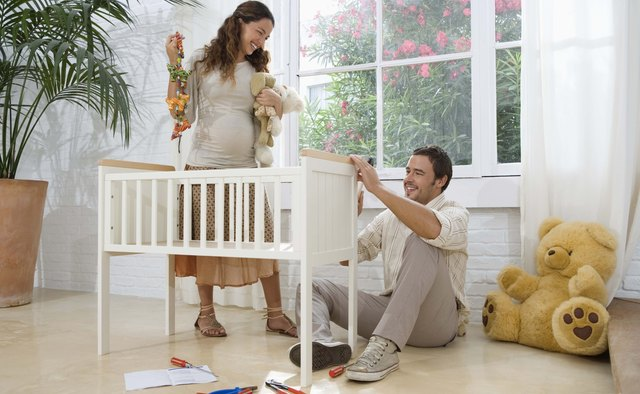 Expecting couple assembling crib