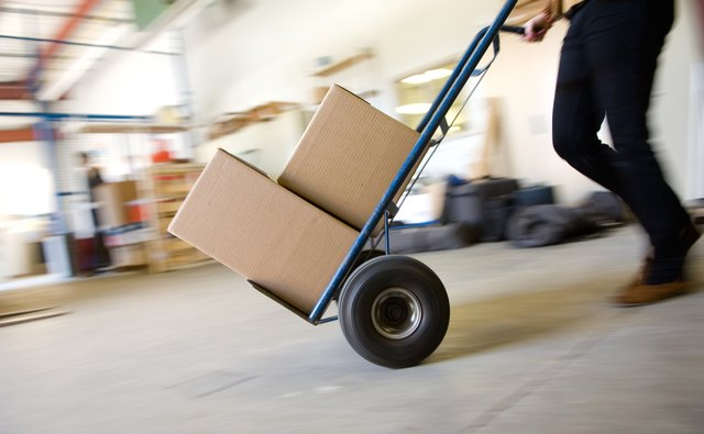 Person pushing hand truck across floor of warehouse