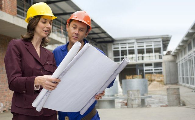 Businesswoman reading blueprints with foreman
