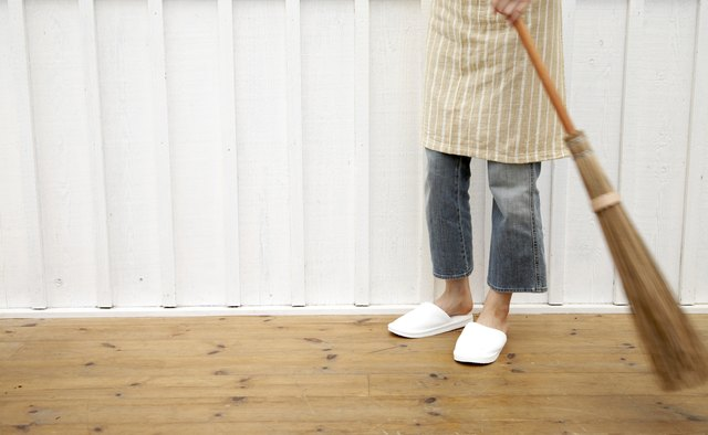 Woman sweeping floor using Japanese style broom in home