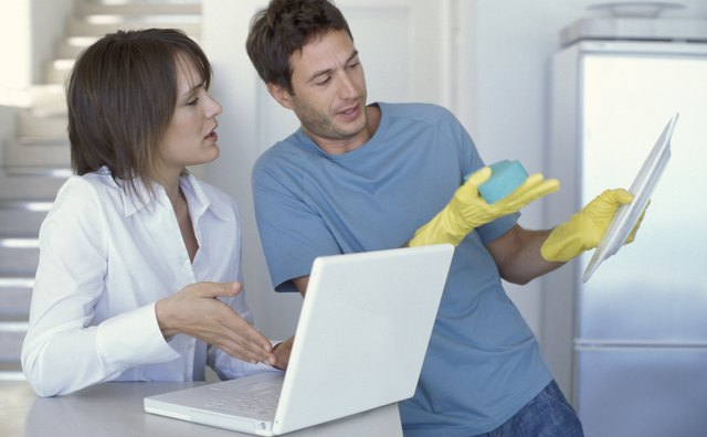 Man washing dishes and woman using laptop