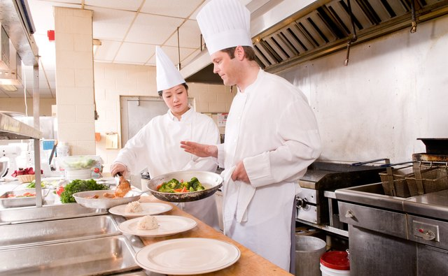 Two chefs serving meal in commercial kitchen