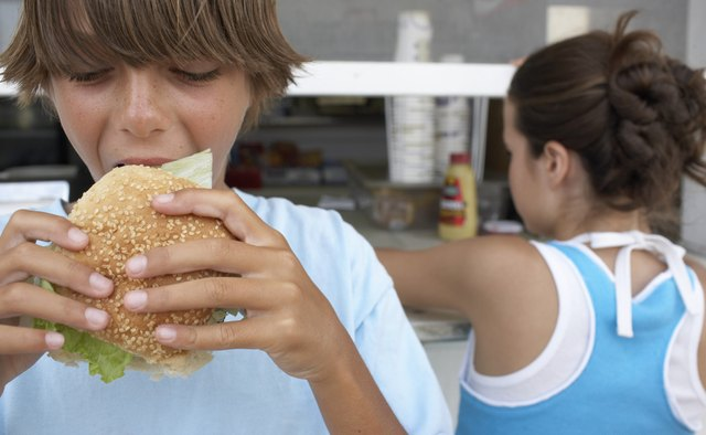 Boy (9-11) eating hamburger, girl (12) queuing at vendor's window