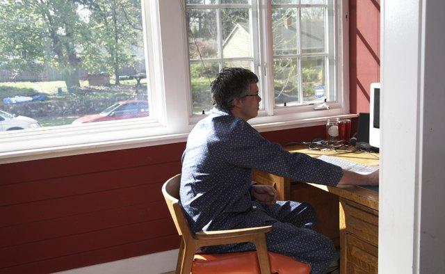 Man in pyjamas using computer at desk in home
