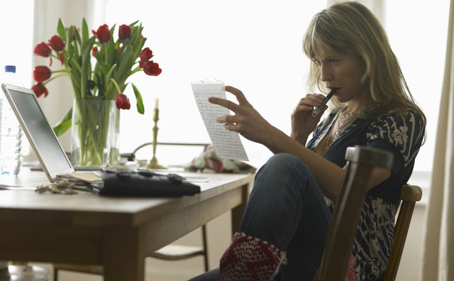 Young woman sitting at dining table reading sheet of paper