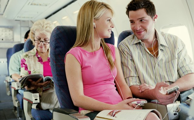 Couple sitting on plane wearing MP3 players, smiling