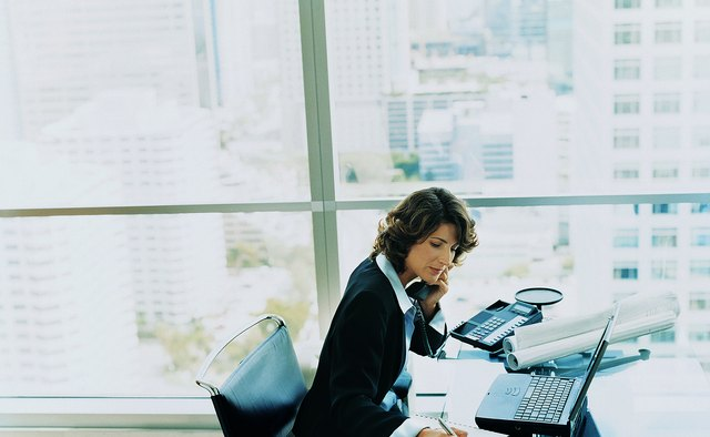 Businesswoman Sitting at Her Desk Using the Phone and Writing in a Notepad