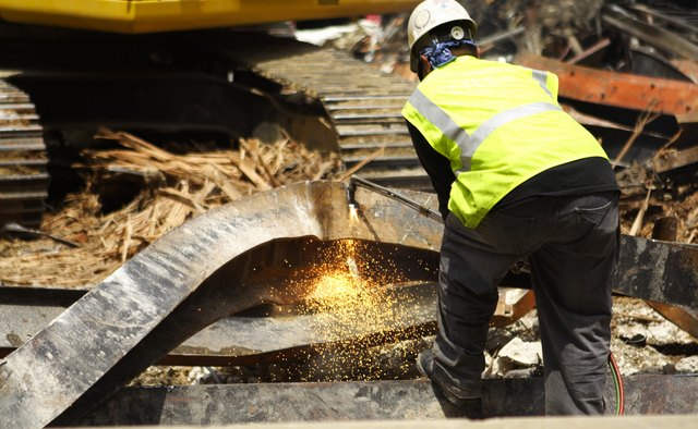 Construction Worker Cutting Scrap Metal Girder Sparks Building Demolition Site