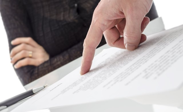 Hand showing a woman to sign the document