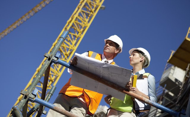 Male and Female Construction Workers Stand on a Platform in a Building Site Discussing a Blueprint