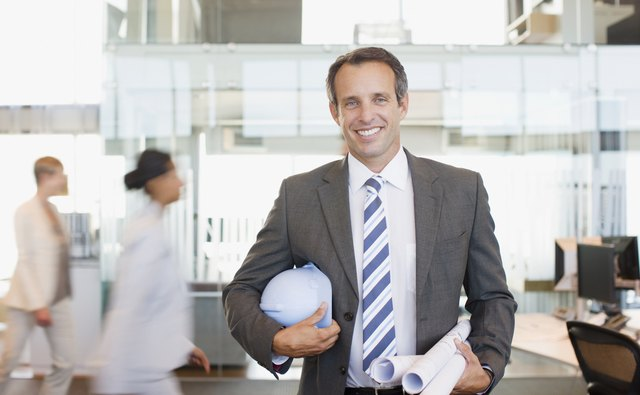 Architect holding blueprints in busy office