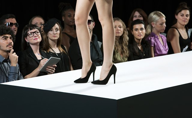 Audience watching model on catwalk at fashion show, low section