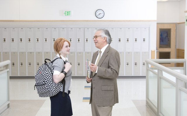 Head teacher talking with school girl (16-17) in school hallway