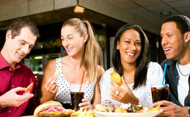 Friends eating hamburger and drinking soda