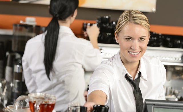 Young waitress cashier giving coffee in cafe