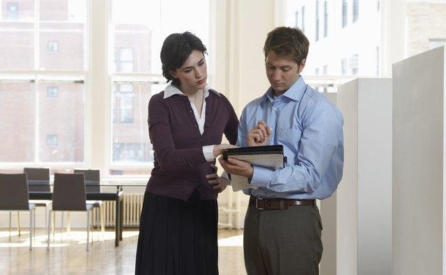 Businessman and Businesswoman Examining a Document in a Folder