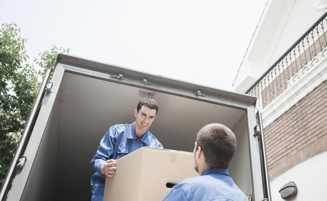Movers unloading moving van, passing a cardboard box