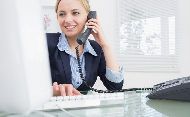 Female executive using phone and computer at office