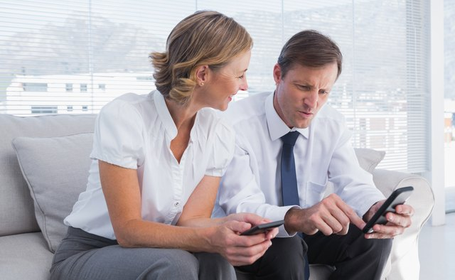 Attractive businessman showing something on his mobile phone to a businesswoman