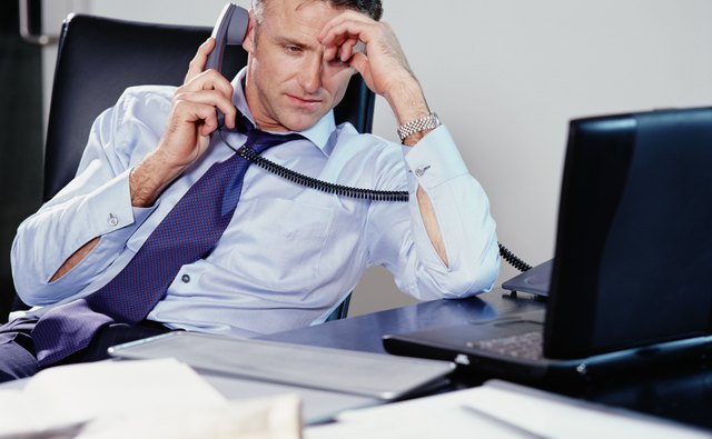 Businessman sitting at desk using phone, resting head on hand