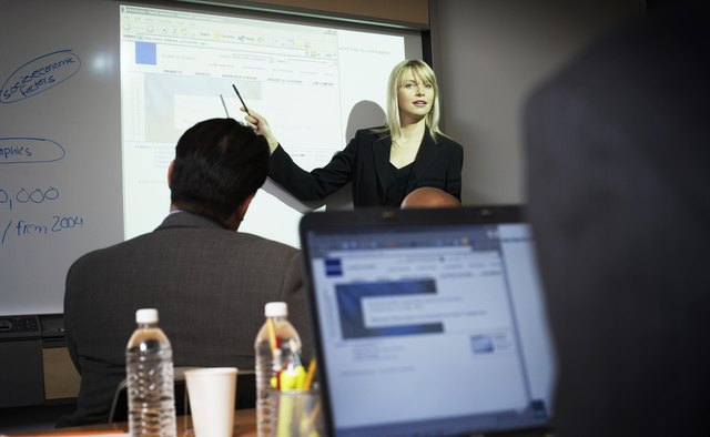 Businesswoman presenting by projection screen, low angle view