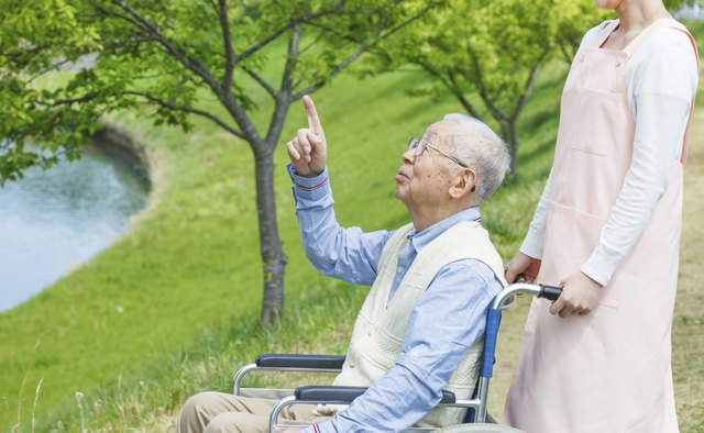 Asian senior man sitting on a wheelchair with caregiver pointin