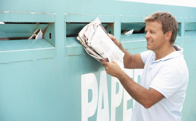Man At Recycling Centre Disposing Of Old Newspapers