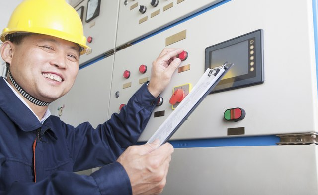Portrait of smiling worker checking controls in a gas plant,