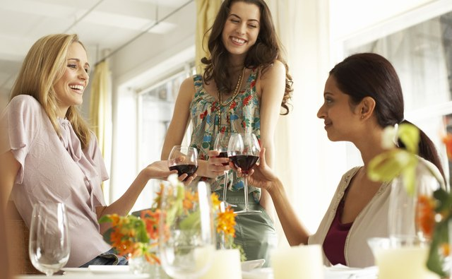 Three women raising glasses of red wine at dinner party, smiling