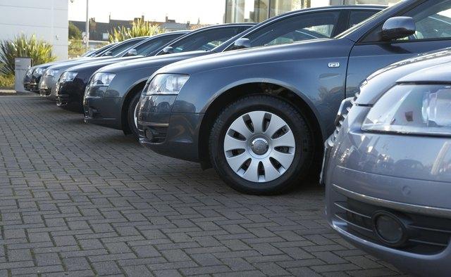 Row of metallic blue cars in car dealer's car park