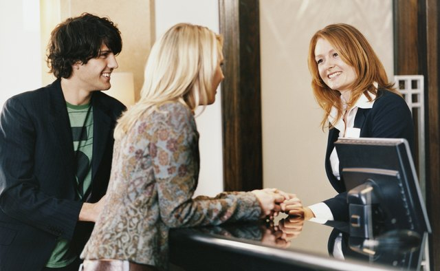 Female Receptionist at a Reception Desk Welcomes a Young Couple to the Hotel