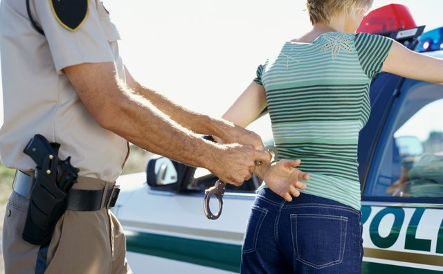 Mid section view of a policeman arresting a young woman