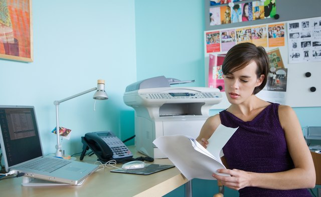 Woman reading document at desk in office