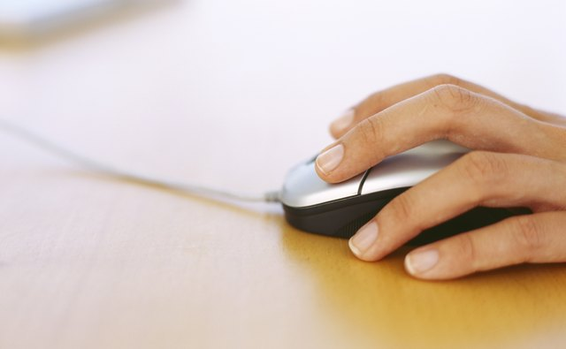 close-up of a human hand holding a computer mouse