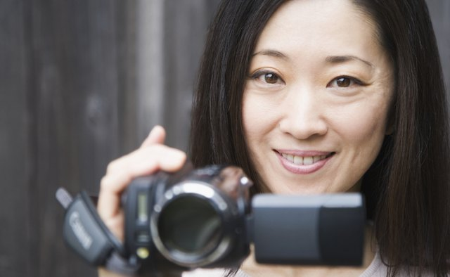 Portrait of a woman holding a home video camera