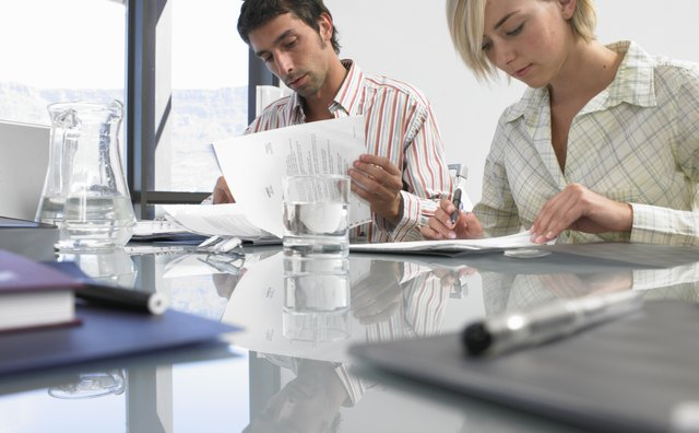 Businesswoman and man sitting at conference table reading documents